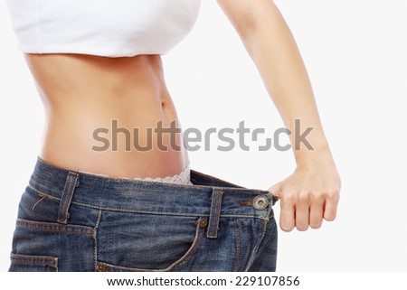 Young slim woman in oversized pair of jeans.  Isolated on the white background #229107856