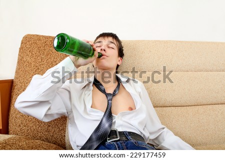 Teenager drinks a Beer on the Sofa at the Home #229177459