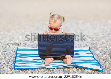 A cute little girl in pink sunglasses sitting on the striped mat with a laptop on the beach on a warm summer day. Holiday on a seashore concept. Funny kids.