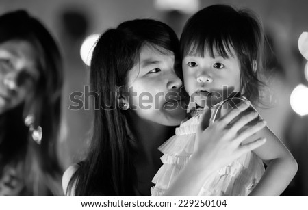 Chiang Mai, NOVEMBER 16, 2013: A young mother is holding her daughter during the Yee Peng lantern buddhist festival in Chiang Mai, Thailand #229250104