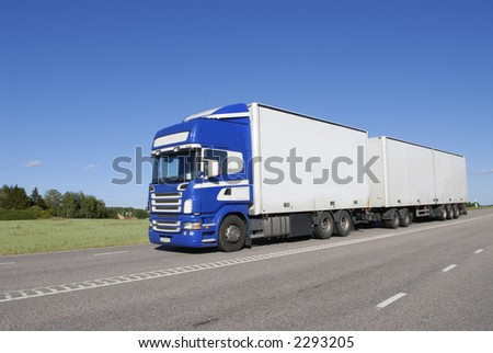 blue and white lorry, truck driving in country-road #2293205
