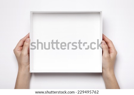 A female(woman, girl) two hands hold the empty(blank) white box isolated white, top view at the studio. #229495762