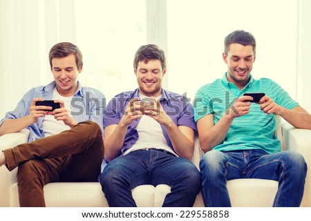 friendship, technology and home concept - smiling male friends with smartphones at home #229558858