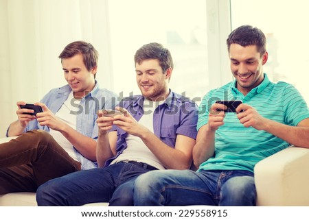 friendship, technology and home concept - smiling male friends with smartphones at home #229558915