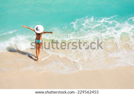 Young woman with arms apart on sand beach #229562455