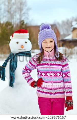 happy kid playing with snowman. funny little girl on a walk in the winter outdoors #229575157