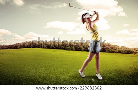 Active woman player hitting the ball on golf court. Sporty female exercising golf play on nature over beautiful landscape background.  #229682362