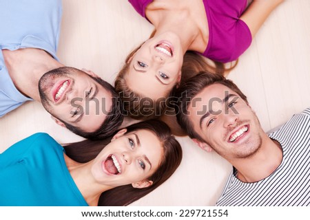 Happy together. Cheerful friends lying down and looking at camera   #229721554