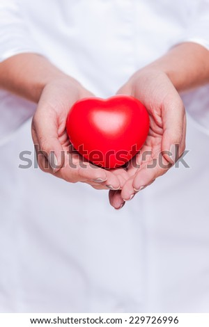Taking good care of your heart. Close-up of female doctor in white uniform holding heart prop  #229726996