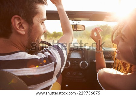 Young Couple Driving Along Country Road In Open Top Car #229736875