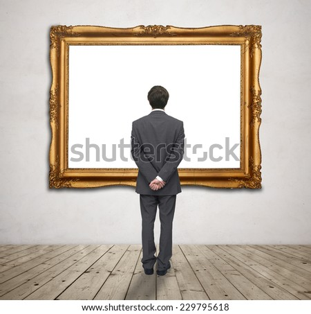 young businessman looking at blank gold frame