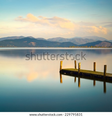 Wooden pier or jetty and on a blue lake sunset and cloudy sky reflection on water. Long exposure, Versilia Massaciuccoli Lake, Tuscany, Italy. #229795831