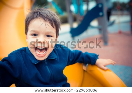 Cute Asian Caucasian mixed race toddler happily playing on a slide in a playground outside in the summer sun #229853086