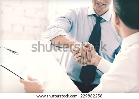 businesss and office concept - two businessmen shaking hands in office Royalty-Free Stock Photo #229882258