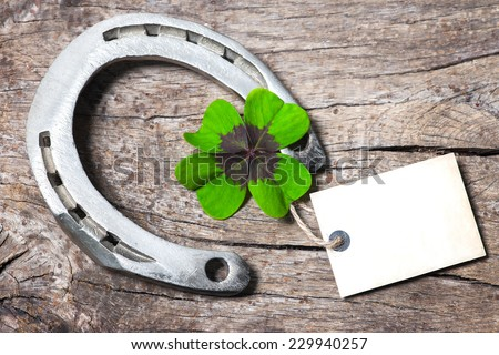 Horseshoe and four leaf clover with empty tag on old wooden #229940257