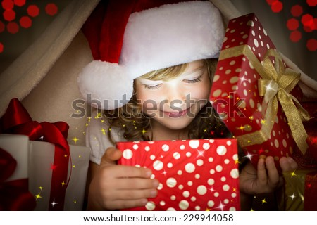 Happy child opening Christmas gift box. Funny baby dressed in Santa Claus hat in bedroom. Portrait of smiling kid at home. Xmas holiday concept