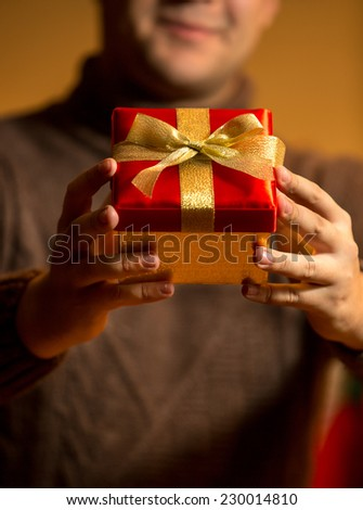 Closeup photo of happy man holding red gift box with golden bow #230014810
