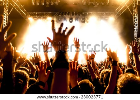 silhouettes of concert crowd in front of bright stage lights #230023771