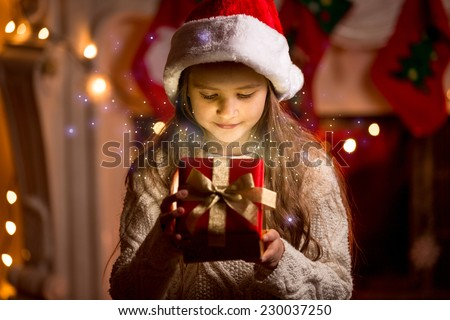 Little cute girl looking inside of glowing Christmas present box
