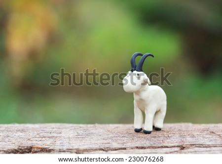 Plasticine world - little homemade white goat stand on a wooden floor, selective focus and place for text