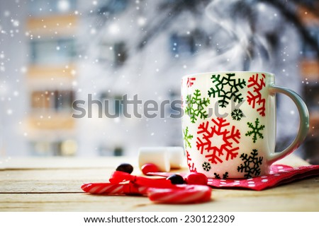 Hot Coffee cup on a frosty winter day window background with candy canes /Christmas holidays background/ Winter cozy background #230122309