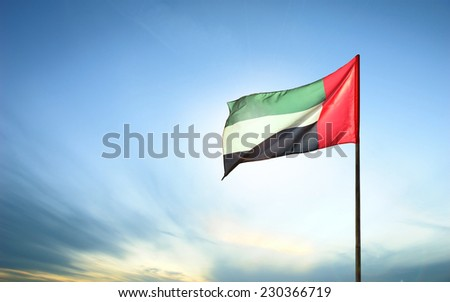 A United Arab Emirates flag flying against clean and tranquil sky. UAE celebrates it's national day on 2nd December every year. Royalty-Free Stock Photo #230366719