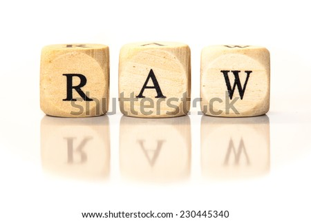 Term RAW spelled from toy cubes, dice letters with reflection on bottom. Studio shot on White background.