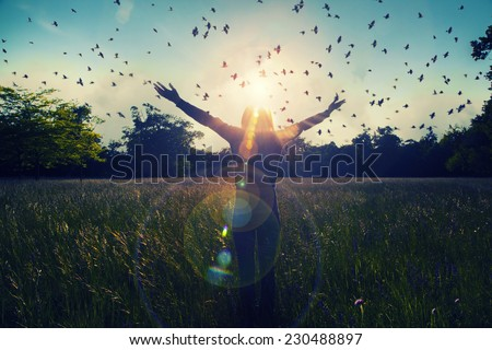 Young girl spreading hands with joy and inspiration facing the sun,sun greeting,freedom concept,bird flying above sign of freedom and liberty  Royalty-Free Stock Photo #230488897