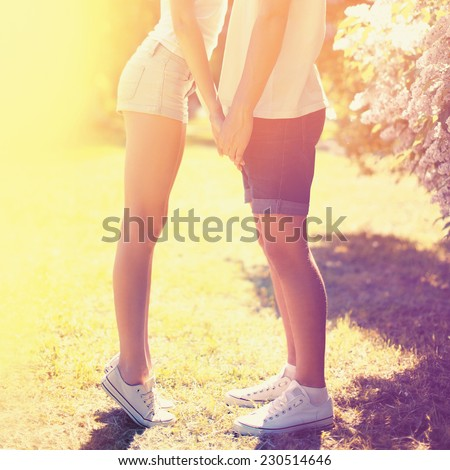 Summer colorful sunny photo happy young couple teenagers in love, guy and girl kissing holding hands outdoors, bright warm colors #230514646