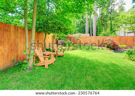 Fenced backyard with green lawn, flower beds and romantic sitting area with wooden chairs and table #230576764