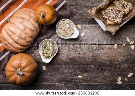 Rustic pumpkins with cookies and seeds on wood. Autumn Season food photo