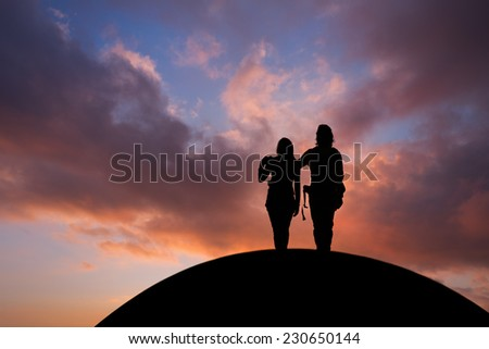 silhouetted couple standing on hill in sunset sky  #230650144