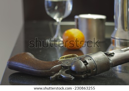 Close up of an armed retro revolver laid on a kitchen table, indoor shot with blurred background #230863255