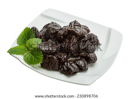 Dried plums with melissa leaves isolated on white #230898706