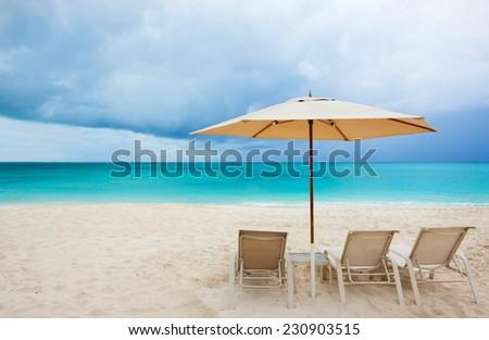 Chairs under umbrella on a stunning Caribbean beach #230903515