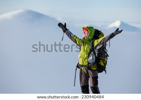 Backpacker woman posing in winter mountains #230940484