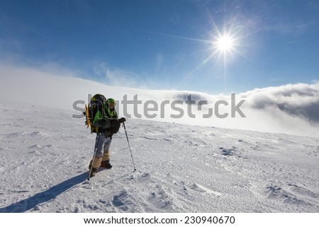 Backpacker man is posing in winter mountains #230940670