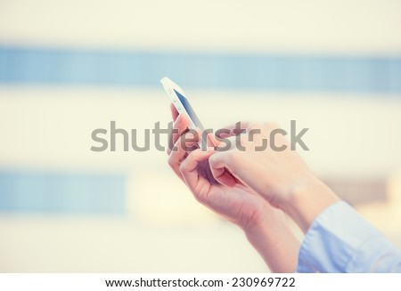 Closeup image woman hands holding using smart mobile phone isolated outside corporate building background. People new generation technology addiction concept. Customer service provider relationship