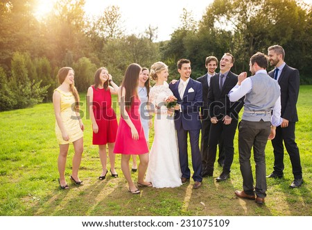 Full length portrait of newlywed couple having fun with bridesmaids and groomsmen in green sunny park #231075109