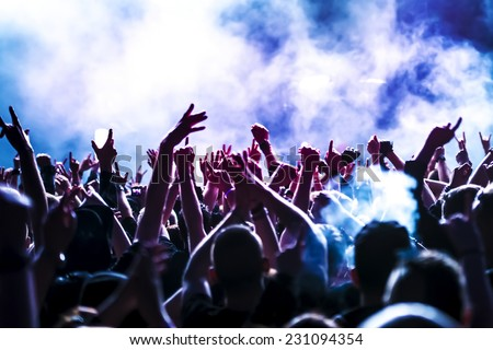 silhouettes of concert crowd in front of bright stage lights Royalty-Free Stock Photo #231094354