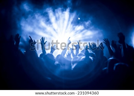 silhouettes of concert crowd in front of bright stage lights #231094360