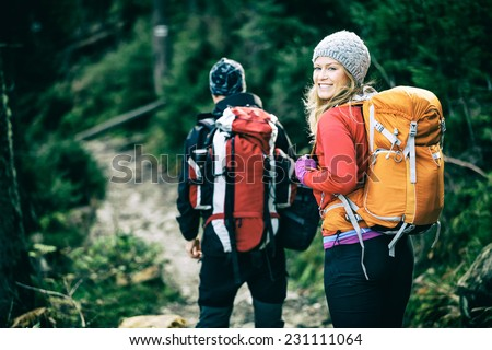 Man and woman hikers trekking in mountains. Young couple walking with backpacks in forest, Tatras in Poland. Old vintage photo style. #231111064