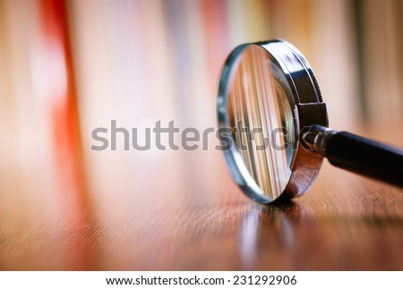 Close up Single Magnifying Glass with Black Handle, Leaning on the Wooden Table at the Office. Royalty-Free Stock Photo #231292906