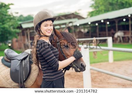 Smiling jockey girl stroking her horse