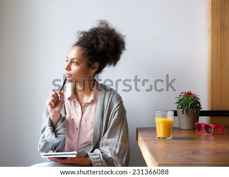 Portrait of a young woman sitting at home with pen and paper Royalty-Free Stock Photo #231366088