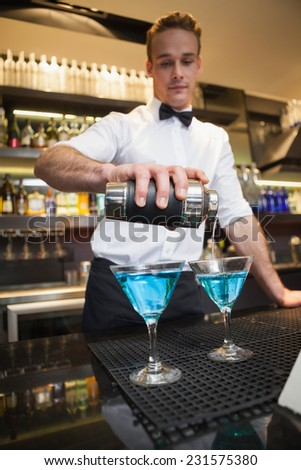 Bartender pouring cocktail into glasses in a bar #231575380