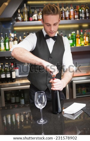 Handsome waiter opening a bottle of red wine in a bar #231578902