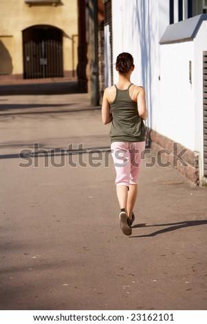Teenage girl jogging away on sidewalk in city #23162101