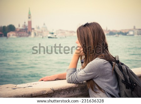 Tourist girl  standing at a marble railing and looking at the sea. Venice. Italy #231636328