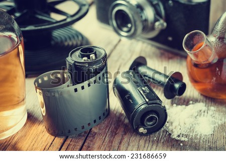 Old photo film rolls, cassette, retro camera and chemical reagents for photographic film. Vintage stylized.